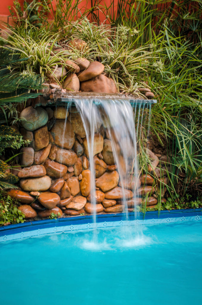 Stacked smooth, round stones with lush foliage surrounding create a small waterfall.