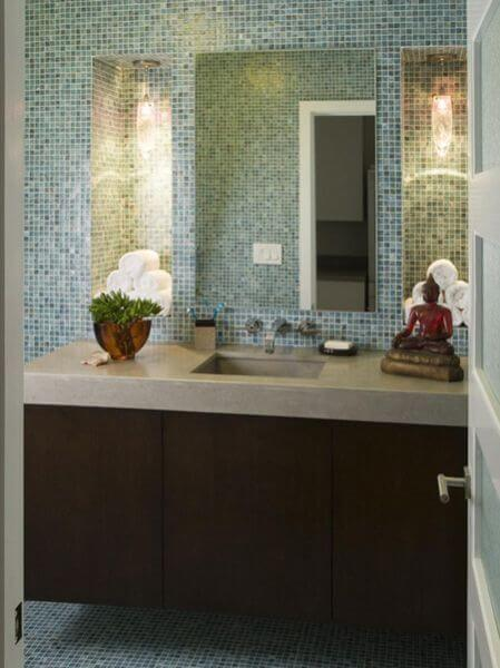 The upstairs bathroom is entirely in glass mosaic tiles and has inset shelves on either side of the mirror that are used as towel storage.