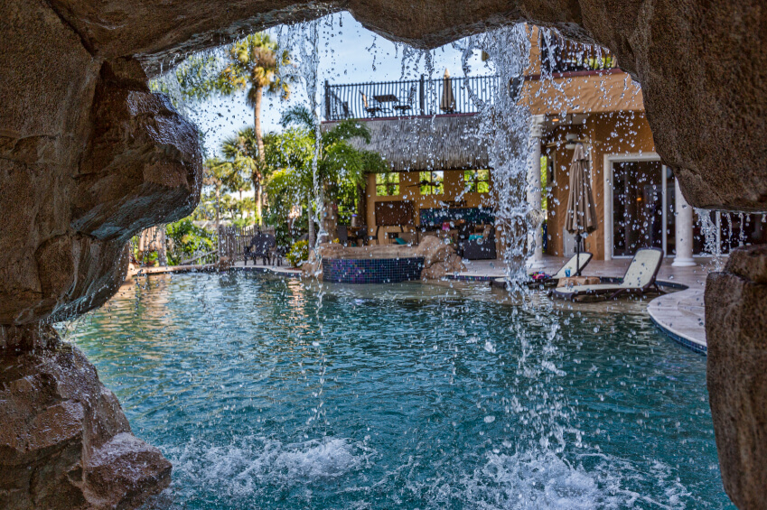 a view of a pool from inside a small cove behind the artificial waterfall
