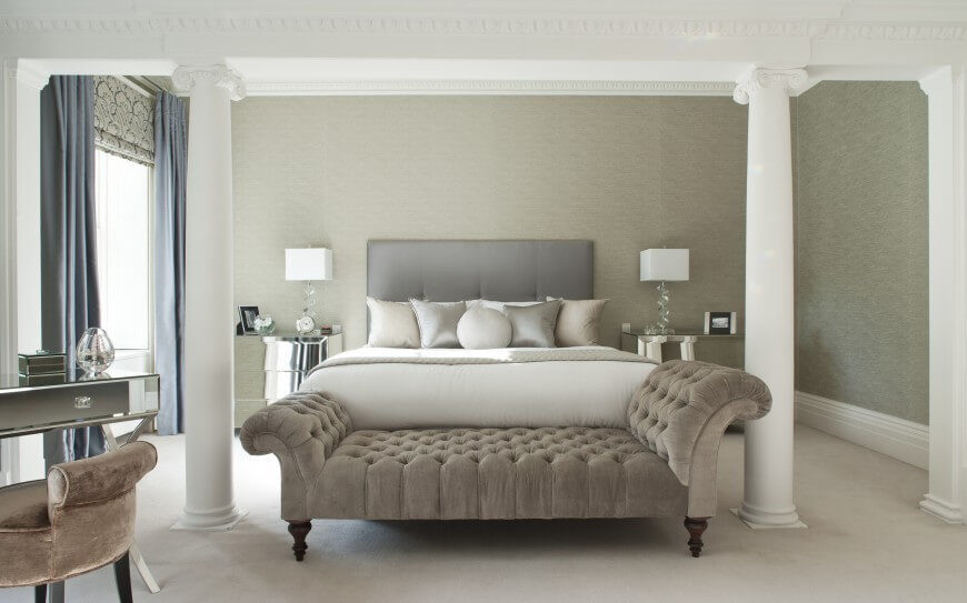 An Elegant Master Bedroom With A Mirrored Vanity And Nightstands The Window Coverings Consist Of
