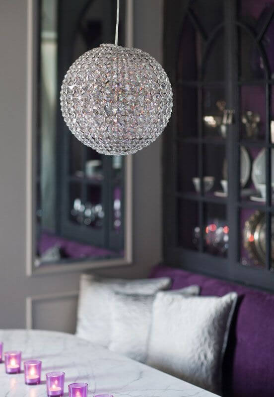 A close up on the dining table, showing the tea light centerpiece and the white marble table top. The most stunning part of this room is the crystal orb chandelier. The back of the china cabinet is painted a coordinating purple.