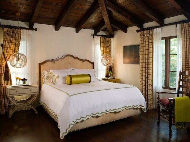 The primary bedroom is a beautiful, old-world space with embroidered, scalloped edged bedding and crystal orb light fixtures hanging above each of the nail-head trimmed nightstands.
