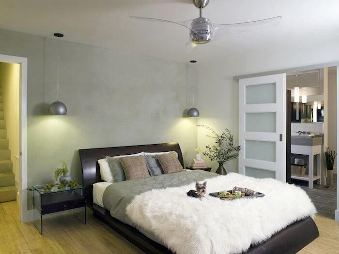 On the lowest level is the master suite. The sleek curved bed frame is topped by silky bedding and a fuzzy blanket. Low glass-topped nightstands have hanging lights above them. A pocket door leads into the master bathroom.