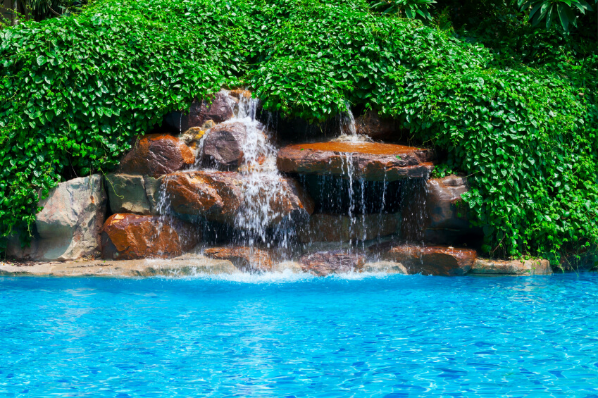 An artificial stone waterfall water feature with thick vines covering the top and sides, hiding any plumbing.