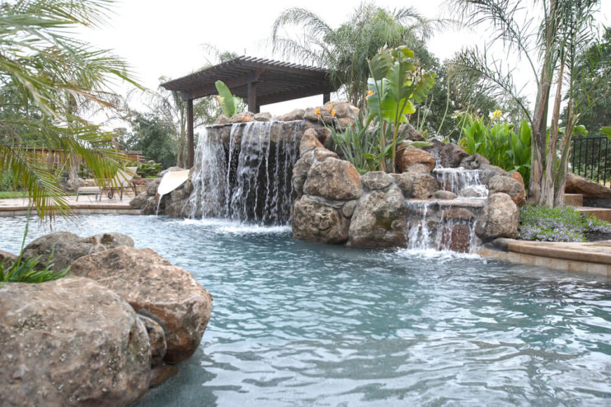 An artificial pool waterfall with large fronds and lush plants decorating the artificial stones. A footbridge with a trellis top leads up to the top of the hill, where a small slide empties into the main pool below.