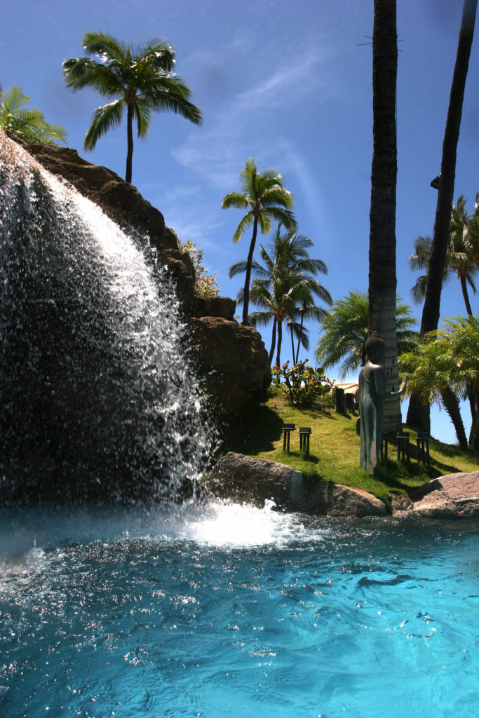 An artificial pool waterfall high above the pool. Visible to the side are palm trees and a stone statue.