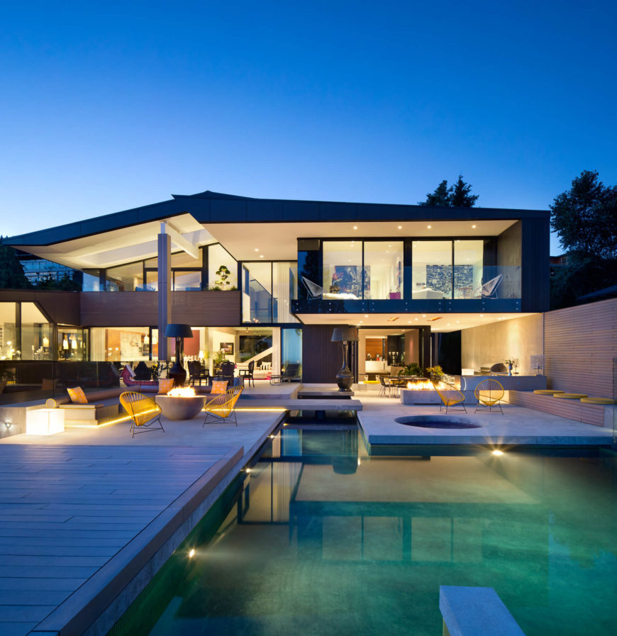The rear of the home opens toward a cornucopia of detail, with concrete and wood patio sections framing a large pool. Fire pits and conversation spaces are overlooked by the rooms featuring floor to ceiling glass panels.