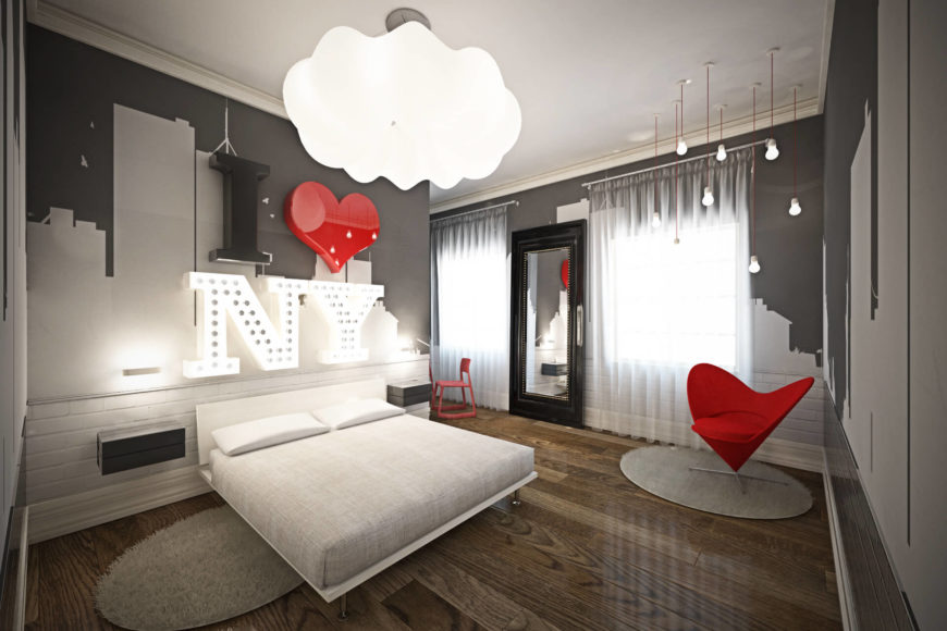 This bedroom makes a clear break with the prevailing style of the home, with grey cityscape wall painting, contemporary furniture, and bold red accents. A heart shaped accent chair mirrors the wall mounted heart above the bed.