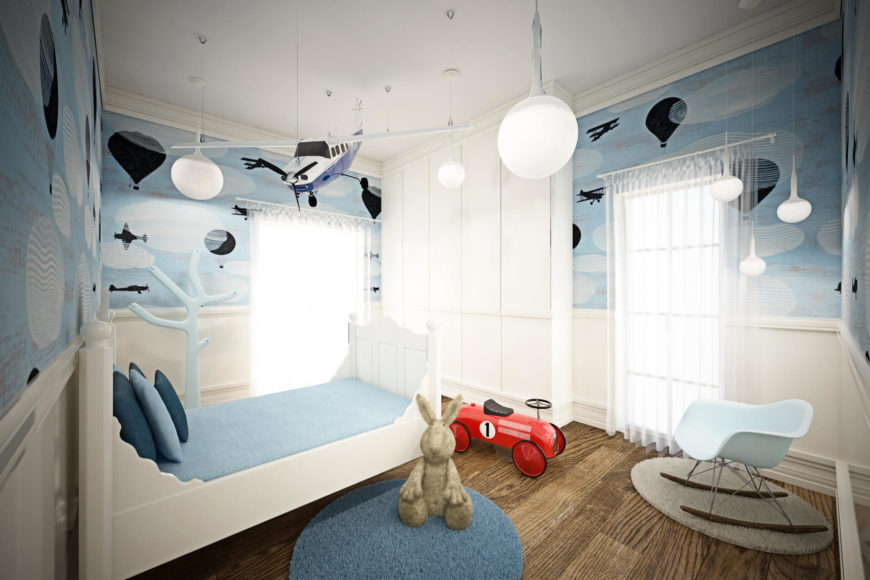 This younger kids bedroom is awash in sky blue and whites, with airplane details painted onto the walls. A series of pendant lights and a model airplane hang above.