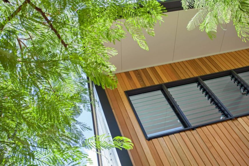Large eaves hang over the upper level louvered windows, for shade in the brightest parts of day.