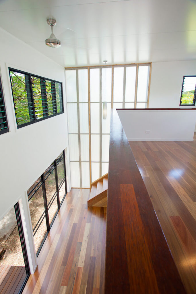 Looking down, we see the expanse of rich hardwood flooring at the bottom of the stairs, sunlit via the floor to ceiling windows. The fiberglass exterior panels allow the home to glow in daylight.