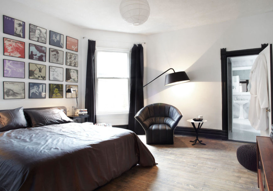 The master bedroom mixes dark hued bedding, drapes, and armchair with light surroundings. A wall-size array of album covers by The Smiths adds a personalized, artistic touch.