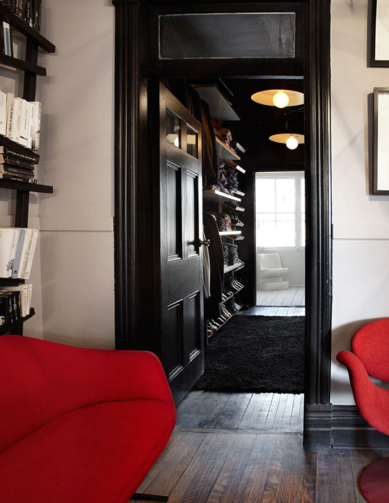 From here we see a lengthy open closet passage toward a bathroom on this upper floor. The black trim contrasts perfectly with white walls for a nuanced look.