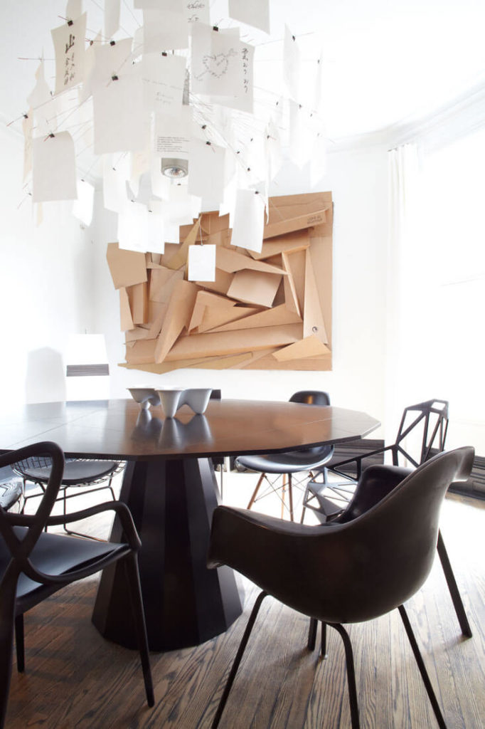 The dining room holds a striking set of decoration: chandelier and large wall-mounted paper sculpture add an ultra-modern touch and sharp visual appeal. Black dining table is surrounded by a mixture of chair styles.