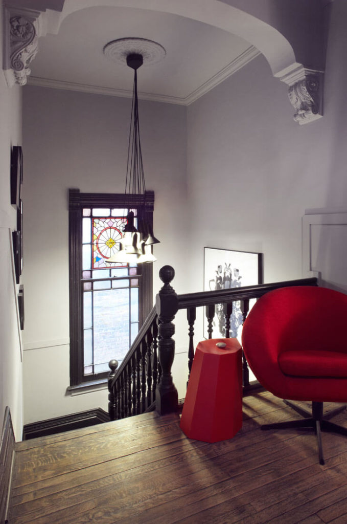 At the top of the staircase we see a unique set of pendant lights before the stained glass window. Bright red modern armchair and table add a burst of color here.