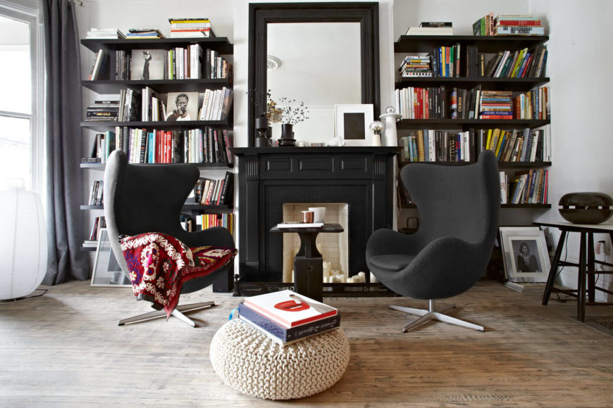 This cozy living room setup perfectly illustrates the eclectic mixture of traditional and modern elements throughout this home. Hardwood flooring meets a black and white space with a black fireplace at center and pair of egg-shape armchairs flanking.