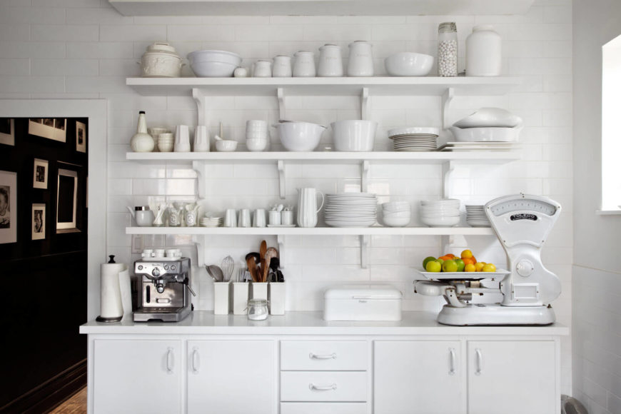 The white cupboards and shelving match sleek white tiling on the wall. All-white dishes create a monotone, minimalist look.
