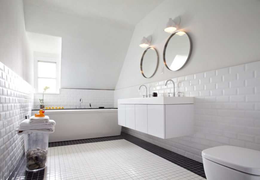This upper floor bathroom houses modern brick tile walls and a minimalist, floating vanity below a low vaulted ceiling.