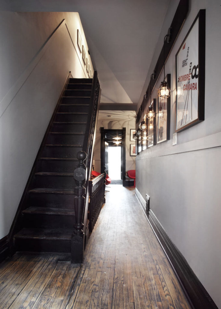 The sprawling hallways of this home are connected by original staircase stained dark, creating a set of repeating colors throughout the home. Bright furniture stands in contrast.