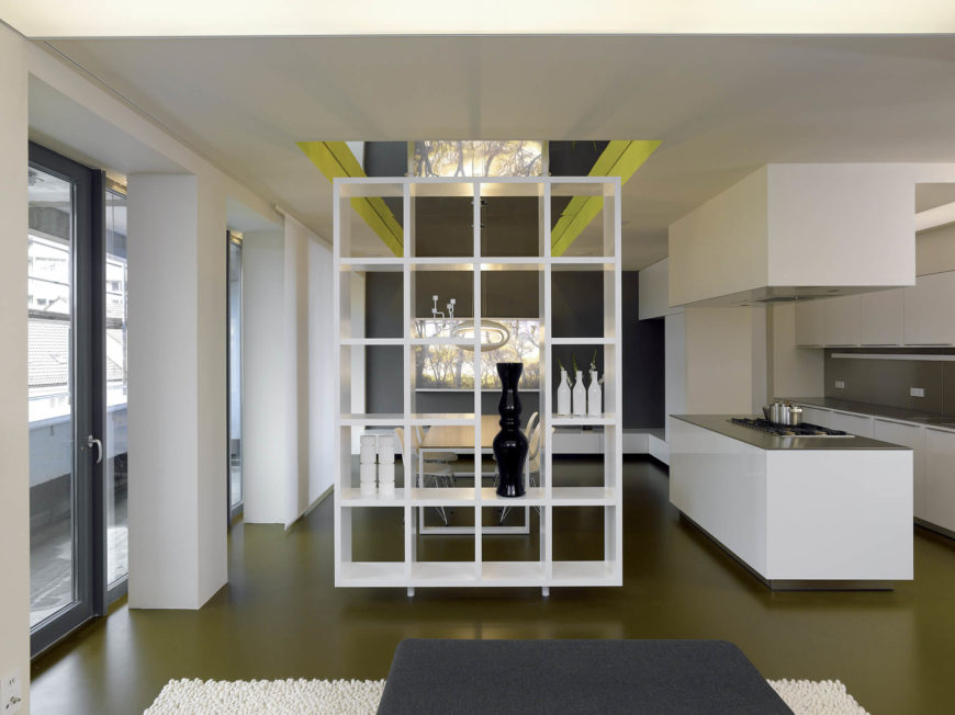 This wider view reveals the contrast between the sleek olive flooring and bold white walls and cabinetry. The free standing shelving provides a mental divide but leaves the visual space open.