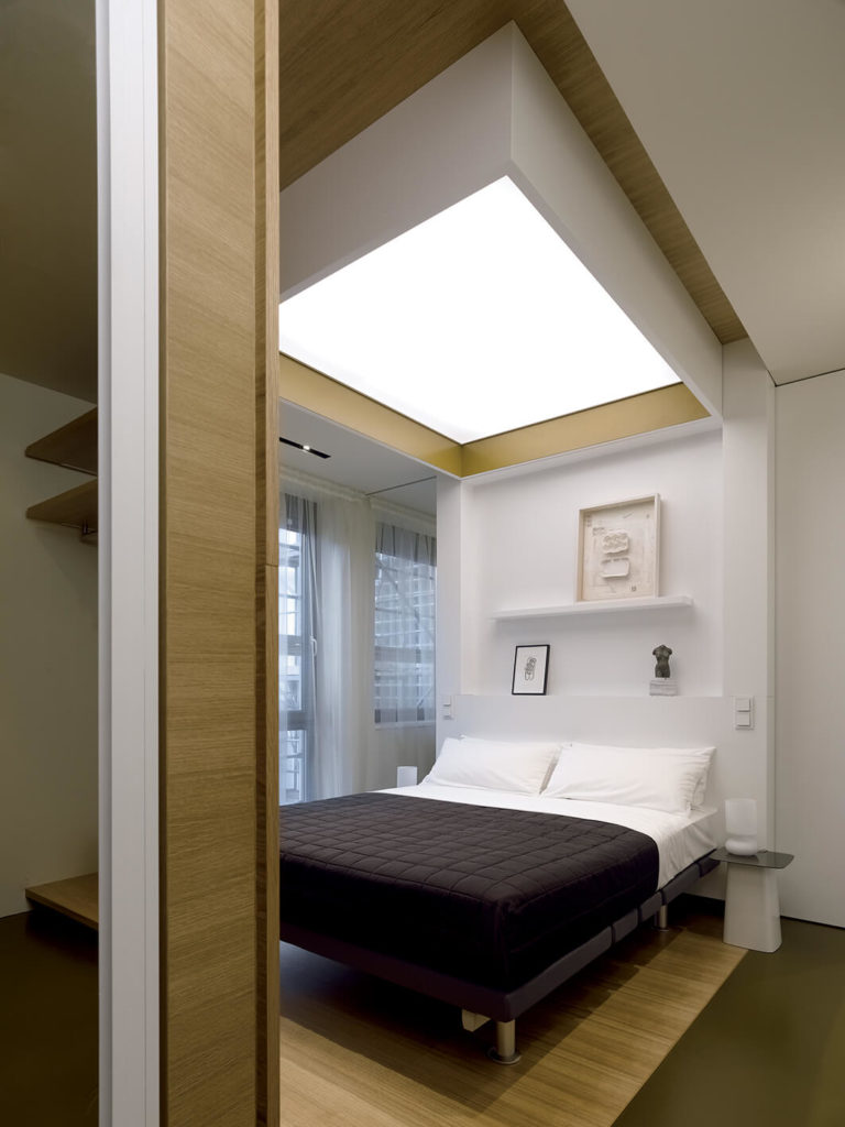 The bedroom houses a bed standing on a distinct area of hardwood flooring, with the dividing wall at the head and diffuse ceiling lighting above.