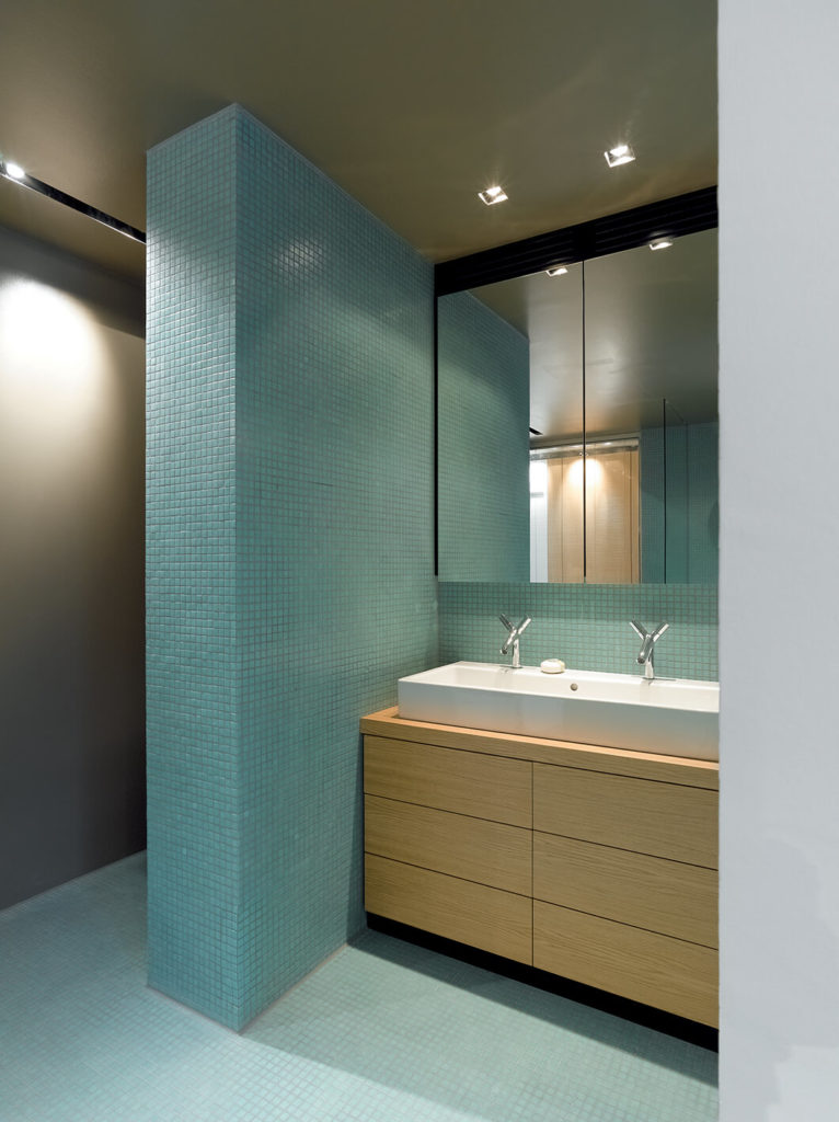The bathroom contrasts its blue tiled floor and walls with a light wood vanity holding a large, dual-faucet vessel sink.
