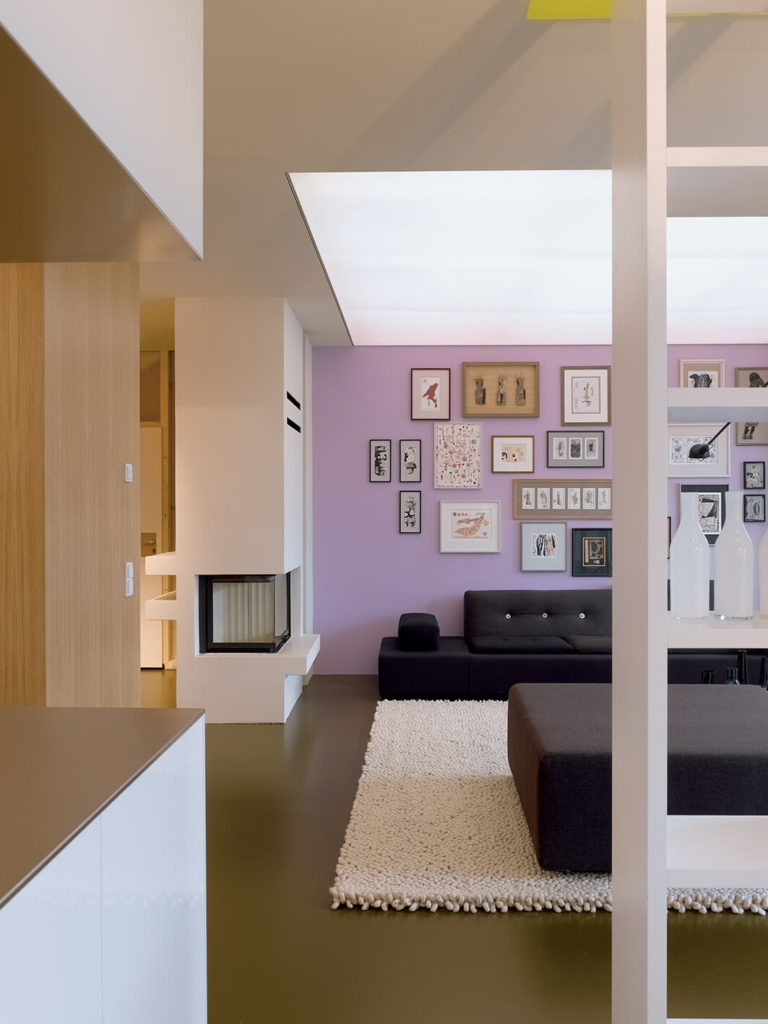 The living room itself stands apart, defined by light purple walls, black seating, and a massive white area rug.