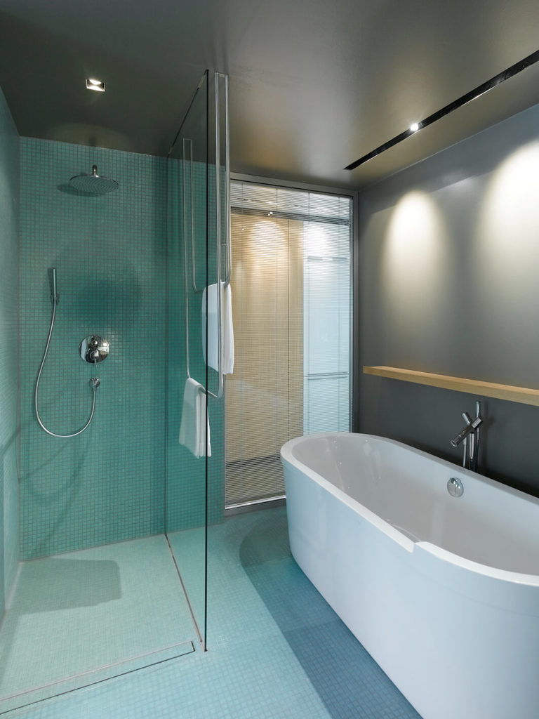 The bathroom also houses a seamless glass enclosure shower and large soaking tub, with a window to the hallway that can be closed via shades.