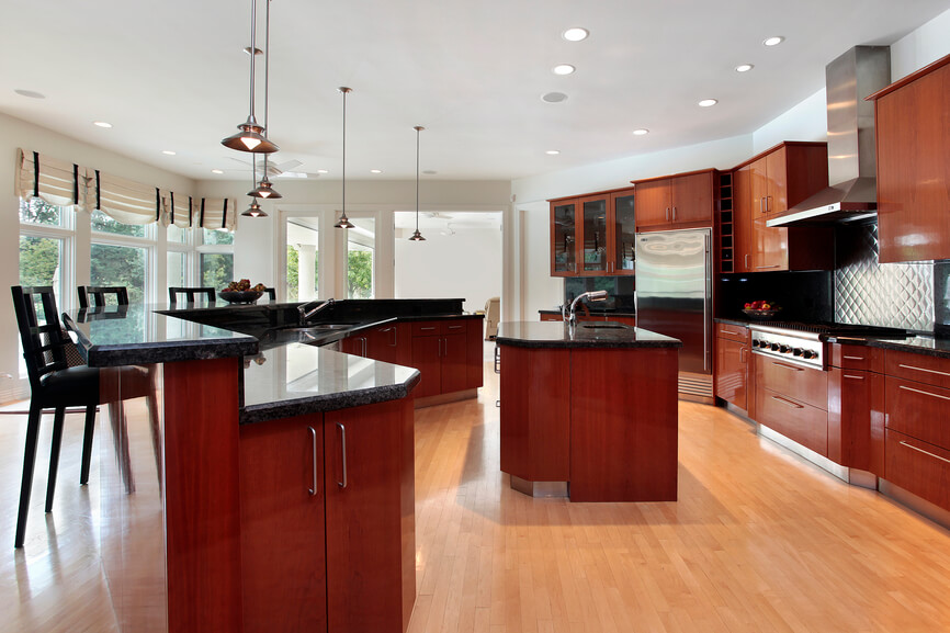 This expansive kitchen see the distinctive red hue used to more subtle effect, with rich natural wood cabinetry seen throughout in a deeply red, but not painted, hue. Light hardwood flooring complements the look, contrasting with black granite countertops. The sprawling space makes room for a large curved island with bar space, as well as a smaller central island for cook preparation.