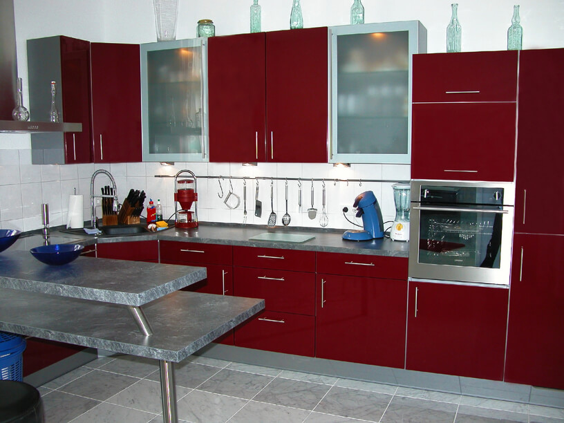This high contrast kitchen features deep red cabinetry, paired with stainless steel hardware and appliances, over neutral grey flooring and countertops. White tile backsplash, along with smoked glass upper cupboard doors, add to the textural intrigue.