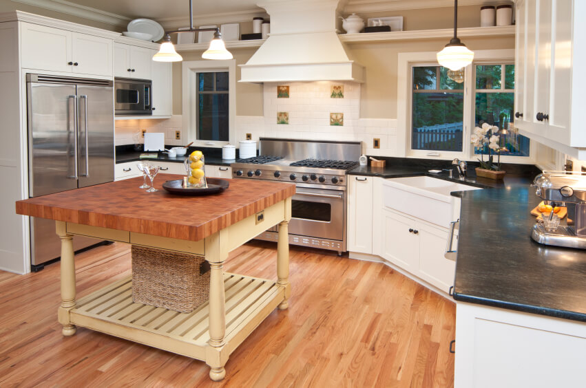 This traditionally styled, open plan kitchen design flaunts pristine white cabinetry and tile backsplash, over bright honey hardwood flooring. A large painted island with thick slab wood countertop is the centerpiece element.