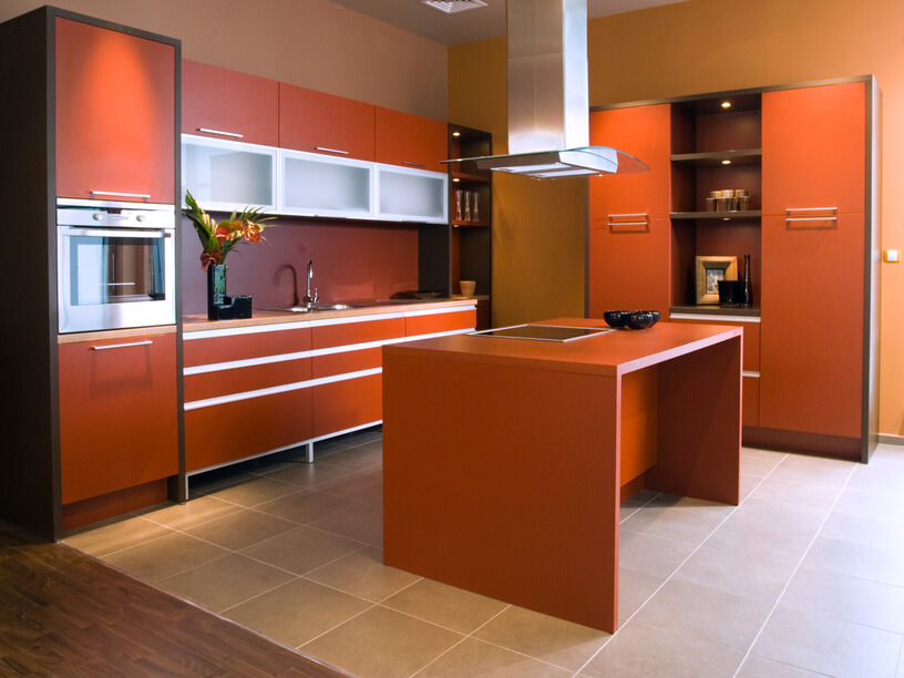 This cozy, open-plan kitchen centers on a nearly orange island, with built-in cooktop. Stainless steel appliances and hardware complement the brightly colored cabinetry over beige tile flooring.