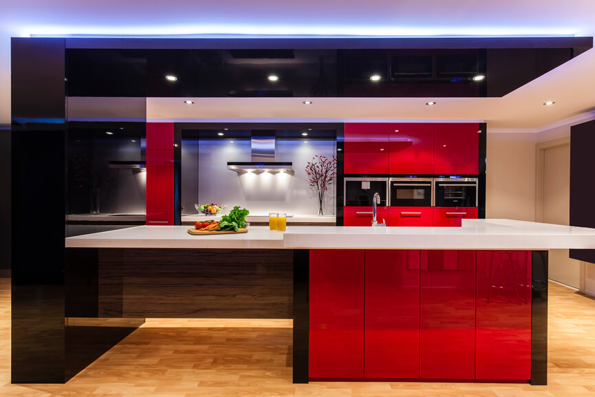 This ultra-modern kitchen boasts reflective red cabinetry, framed in sleek black, over rich natural hardwood flooring. A massive island at center contains both dining space and built-in sink, while innovative lighting ensures the space glows.