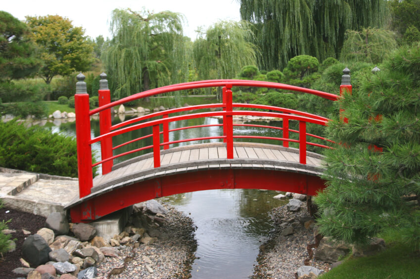 Another instance of a smaller wooden garden bridge in bold Chinese red. The bridge spans the gap between two higher points over a narrowing stream connected to a pond.