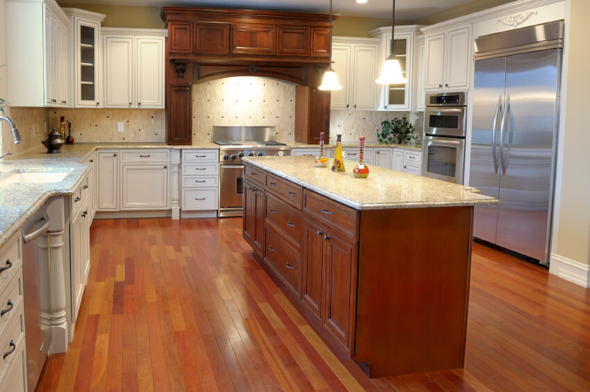 In another wide expanse of a kitchen, a large natural wood island stands with granite countertop. Bold, warm toned hardwood flooring contrasts with bright, intricate cabinetry and a light tile backsplash.