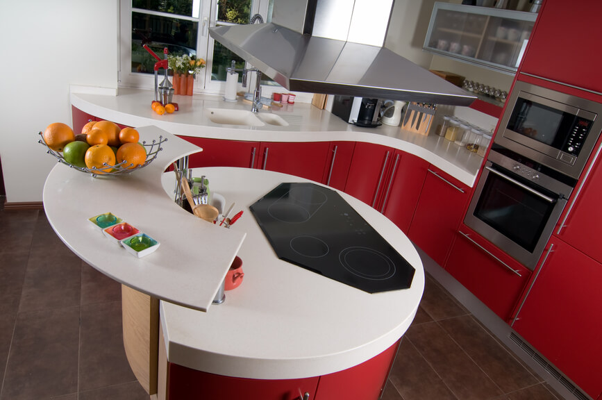 This kitchen features a truly unique circular island, with built-in range and upper-level platform for in-kitchen dining or serving. The sleek, curved white countertops complement rich red cabinetry and large format brown tile flooring.