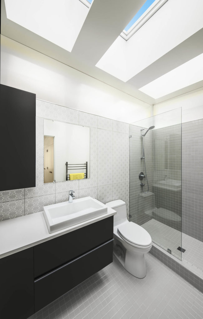 The bathroom features highly textural flooring and walls, with a walk in shower and floating vanity beneath a set of broad skylight windows.