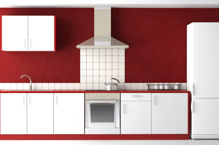 This striking kitchen boasts red and white in equal measure, with pristine white cabinetry and refrigerator wrapped in red. A slim white tile backsplash floats up toward a sleek metal hood vent at center.