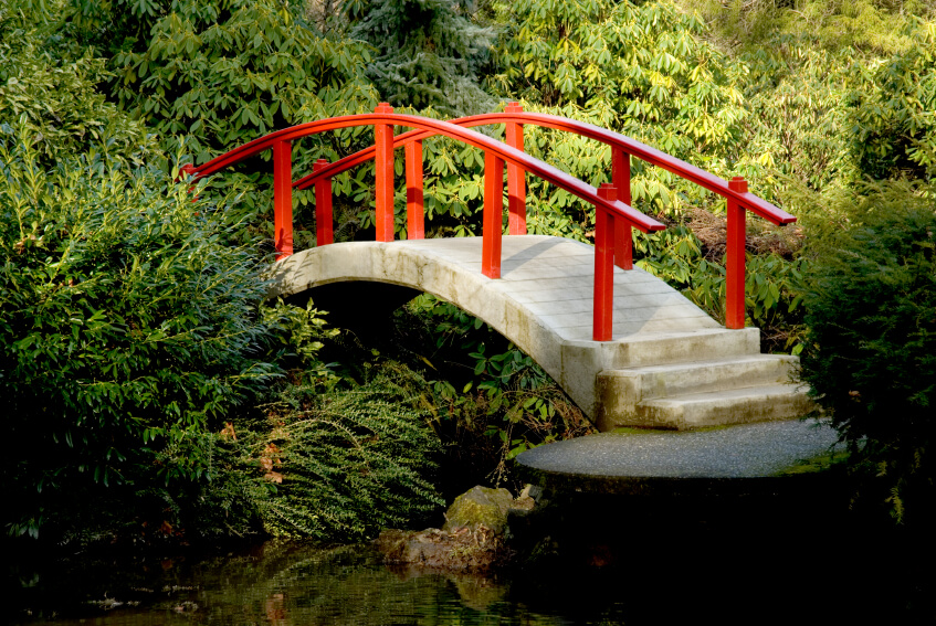 Yet another Chinese red bridge, this time with concrete steps and a walkway. The bridge seems to disappear into a lush, thick forest.