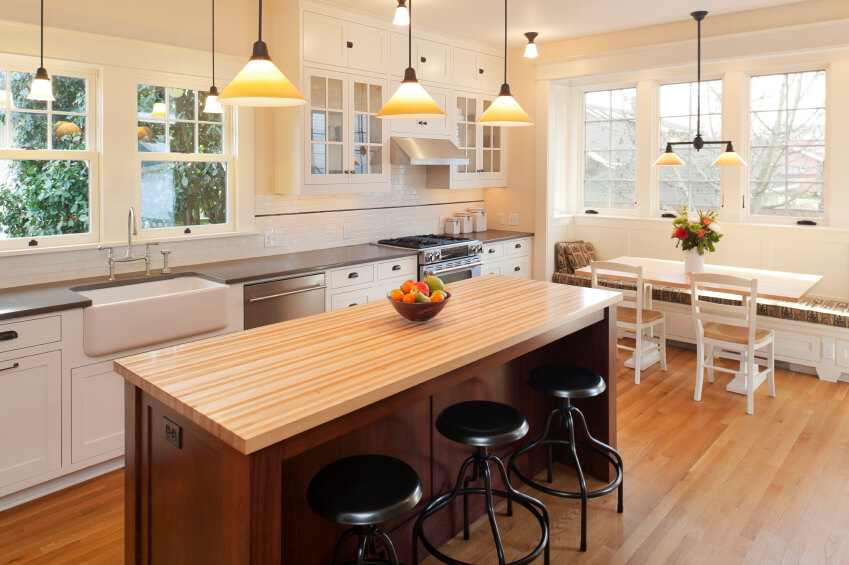 In a wide kitchen naturally lit by several large windows, the honey toned hardwood flooring and island countertop help the white cabinetry truly pop. A small breakfast nook sits tucked beneath the window at right.