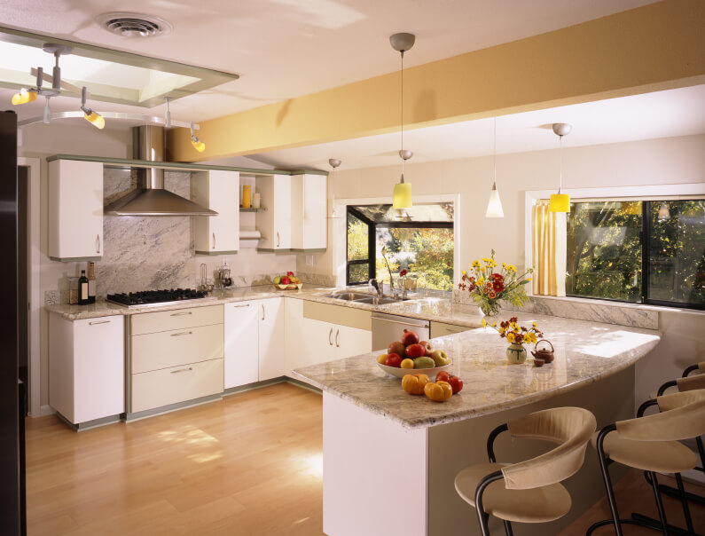 In this modern, sleekly appointed kitchen we see the careful deployment of white cabinetry, juxtaposed against light marble countertops and backsplash. A skylight and box windows pour sunlight over the hardwood flooring.