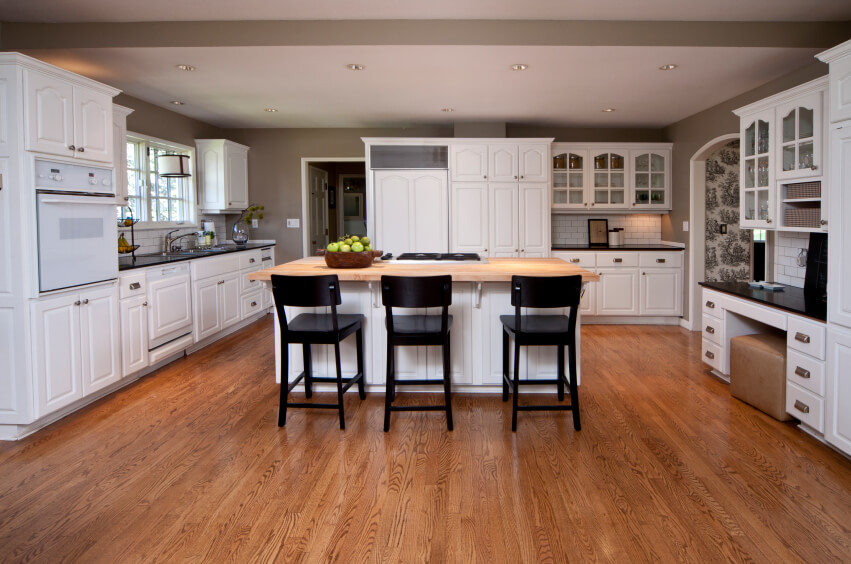 This truly expansive kitchen holds a large white island with natural wood countertop amidst a sea of rich hardwood flooring. White cabinetry and tile backsplash contrast sharply with black countertops all around.