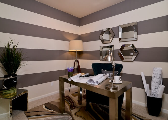 The home office stands apart with sharp horizontal lines wrapping the entire room. Mirrored surfaces abound, from the table to wall hanging pieces, around a thick, minimalist desk.