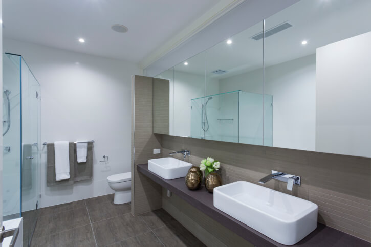 This bathroom features a high contrast between pristine white tile - 32 Bathrooms With Dark Floors