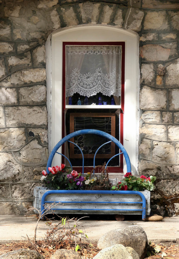 A window low on the wall can have a window box too.This wooden box is held up by an upcycled child's headboard and footboard.