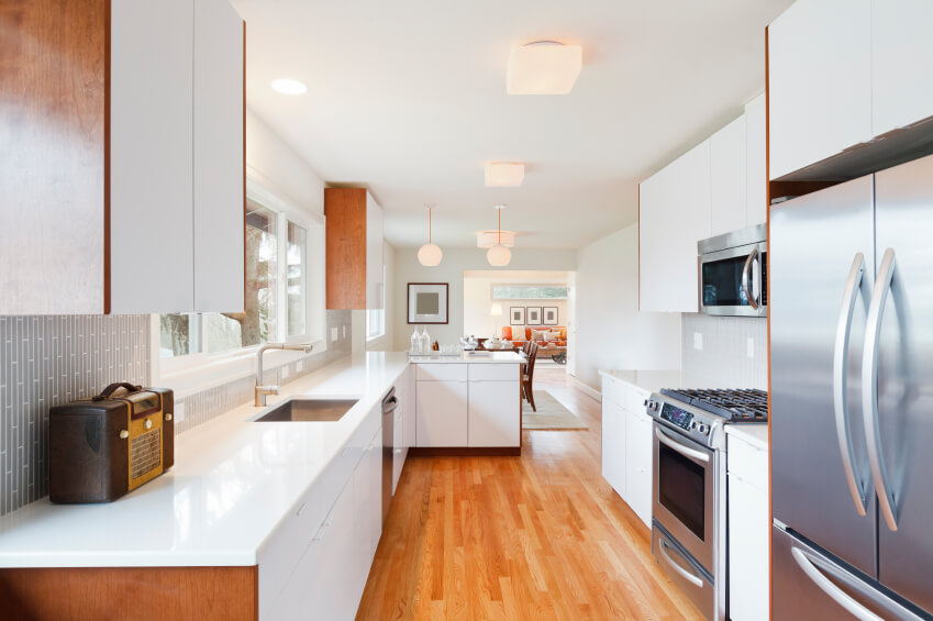In a lengthy, open plan kitchen, the bright and warm wood flooring anchors a mostly pristine white space. Sleek, glossy countertops and cabinetry reflect even more brightness from the expansive windows mounted above the sink.