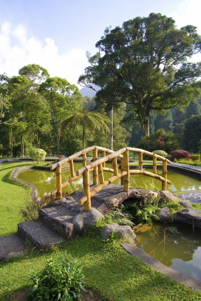 This incredible and unique bridge is made out of artificial stone and untreated pine, connecting two sides of a mosaic walkway over a man-made canal and pond.