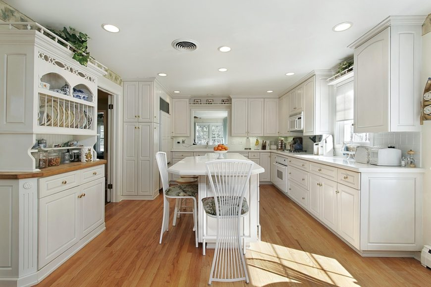 In a large kitchen centered on a lengthy white island, the expanse of honey toned hardwood flooring connects the wide array of bright white cabinetry. White tile backsplash and countertops enhance the bright and open style.