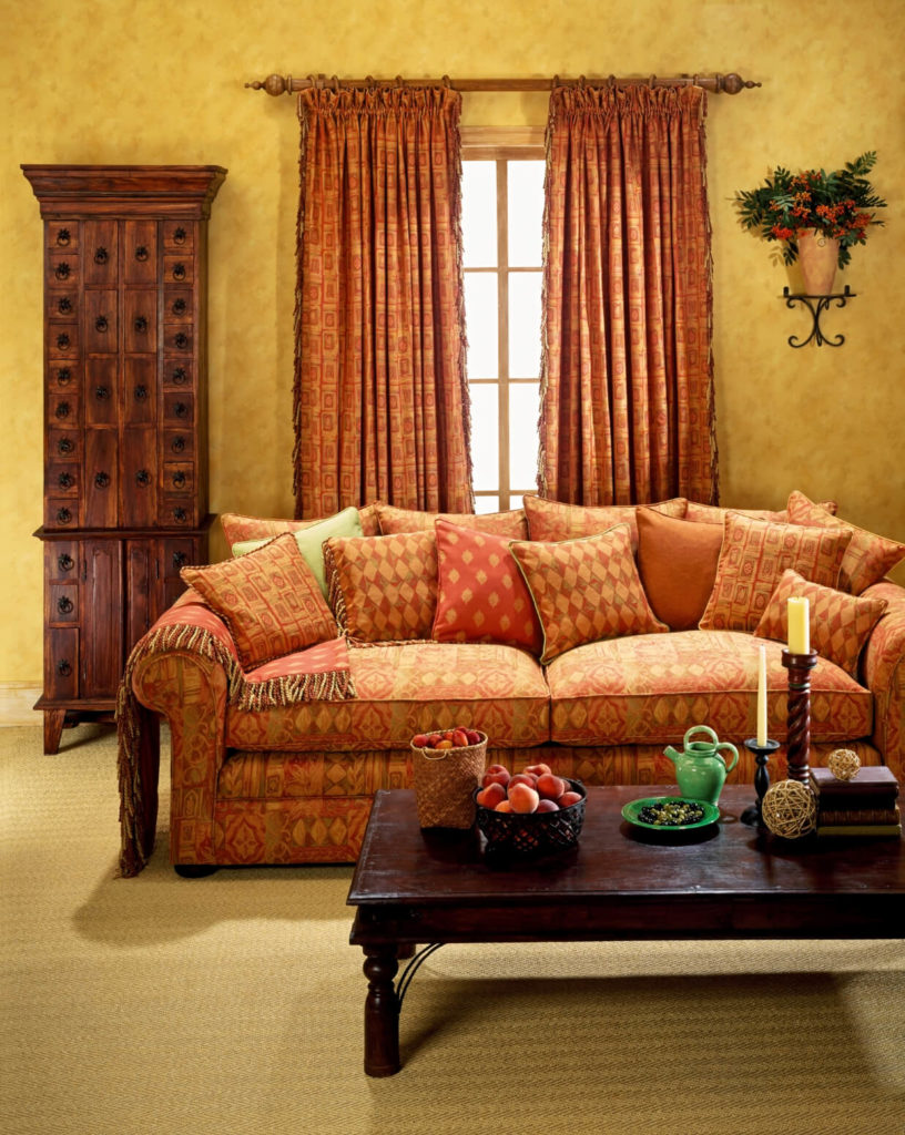 a subtle geometric pattern in the curtains complements the array of patterns on the sofa and