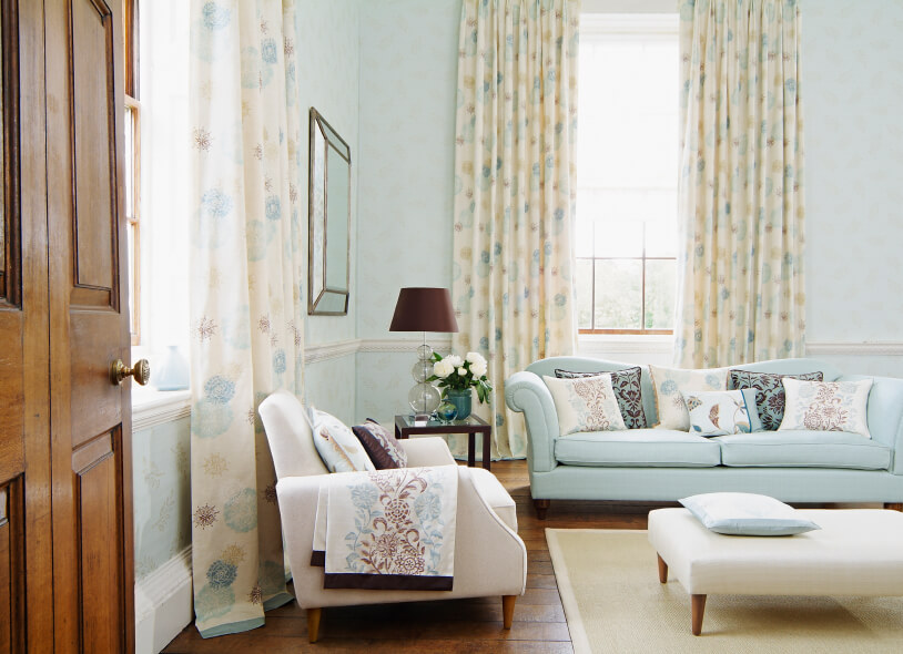 Light Blue Living Room With Patterned Curtains.